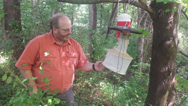 Scott Krans, administrator of the DEP's Office of Mosquito Control Coordination, explains how a mosquito trap works at the Alexauken Wildlife Management Area in West Amwell.