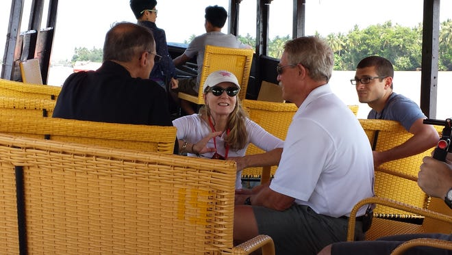 """Filming on the Mekong River in Ben Tre Provence in Vietnam are Mary Ann Koenig in the middle; retired SEAL Capt. Rick Woolard (right); Mike Hixenbaugh, correspondent for Virginia Beach Pilot (far right); and retired SEAL Capt. Robert """"Pete"""" Peterson (left, back to camera)."""