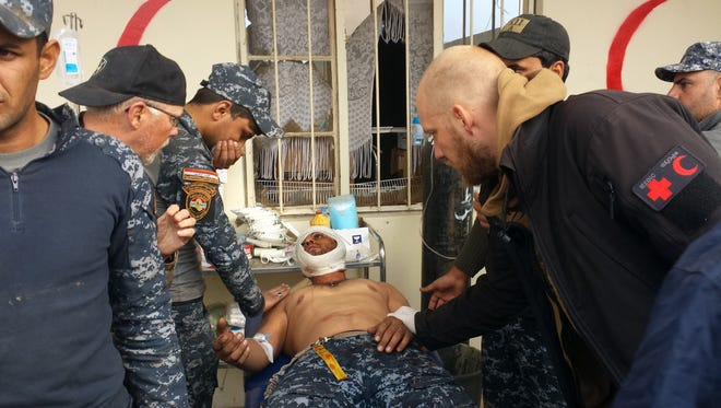 A wounded Iraqi Federal Police trooper is given first aid at a field hospital in Abu Saif village.