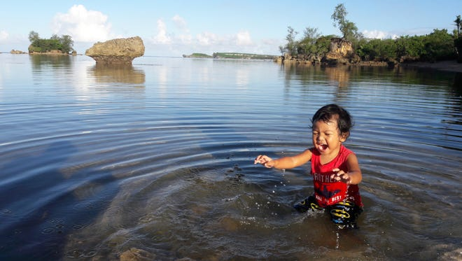 Joey Guban, 2, plays in the waters behind Inn on the Bay Apartments in Agat, Nov. 2017.