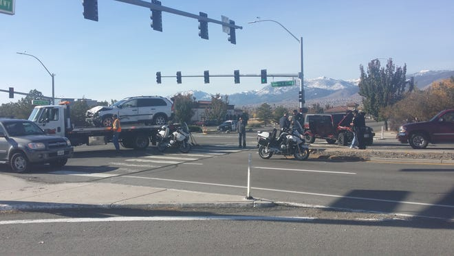 Reno police at the scene of a crash between an unidentified SUV and a Jeep Wrangler near South Meadows Parkway and Double R Boulevard on Monday morning.