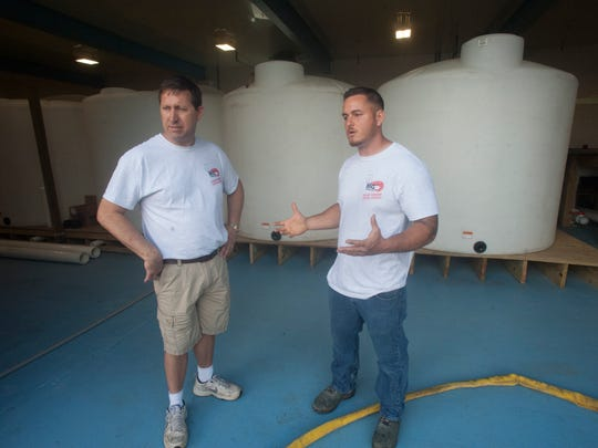 John DiPietropolo Jr. left, and Eric Fusco talk about their indoors shrimp operation at the Big Shrimp Company in Pennsauken.