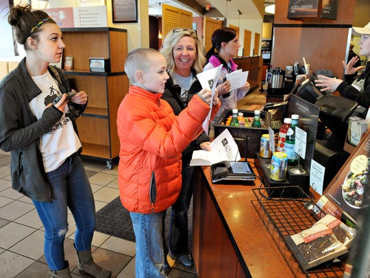 Malachi Neal, 11, holds up his coupon for a fundraiser