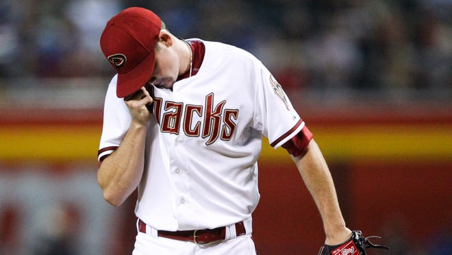 Diamondbacks pitcher Allen Webster (27) wipes sweat from his eye during the first inning against the Los Angeles Dodgers on June 29, 2015.