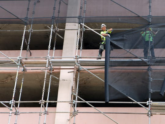 Workers secure netting to catch demolition debris during