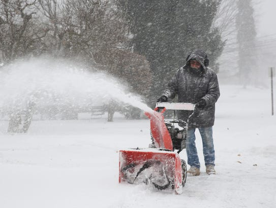 Jim Ferranto clears his driveway with a snowblower