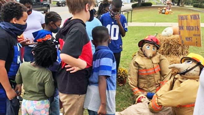 Students from the DIG afterschool program explore the scarecrows along the rail trail in downtown Williston, including this motion-activated one set up by the Williston Fire Department.