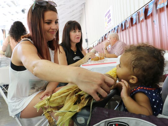 From left, Joanna Taylor, of Pleasant Valley, serves her daughter, Hannah an ear of corn at the Dutchess County Fair in Rhinebeck on Tuesday. Taylor's mother, Pam Foster, of the City of Poughkeepsie is in the background enjoying some fried mushrooms.