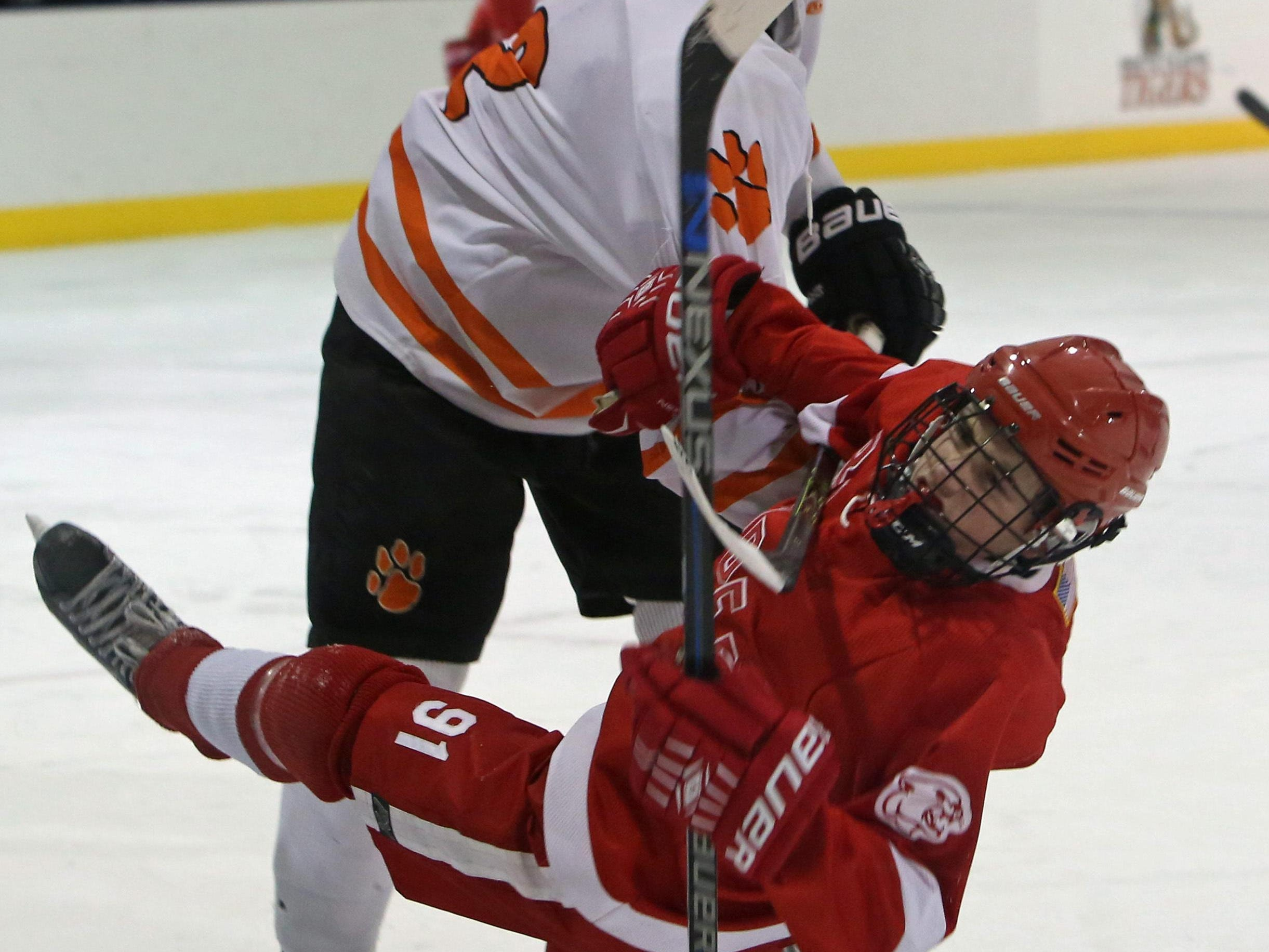 White Plains' James Garnett hits North Rockland's Chris Hilliard during a game at Ebersole Ice Rink in White Plains on Thursday. The teams skated to a 4-4 tie.