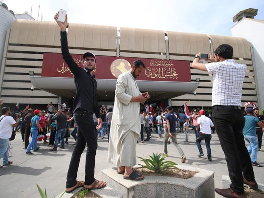 Iraqi protesters enter the parliament after breaking