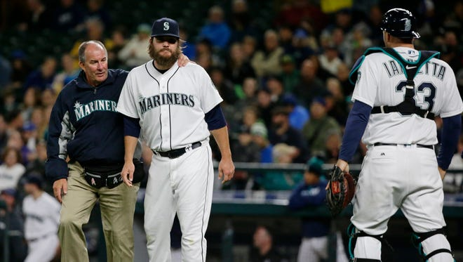 Seattle Mariners starting pitcher Wade Miley, second from left, stands with trainer Rick Griffin, after Miley collided with catcher Chris Iannetta, right, as they tried to field a bunt single by Texas Rangers' Delino DeShields during the third inning of a baseball game, Tuesday, April 12, 2016, in Seattle. (AP Photo/Ted S. Warren)