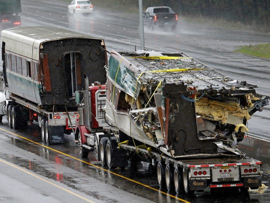 Two damaged train cars sit on flatbed trailers after