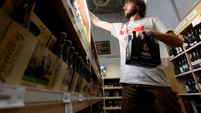 In this Thursday, July 2, 2015 photo, Glen Simister stocks beer at the Utah State Liquor Store in Holladay.