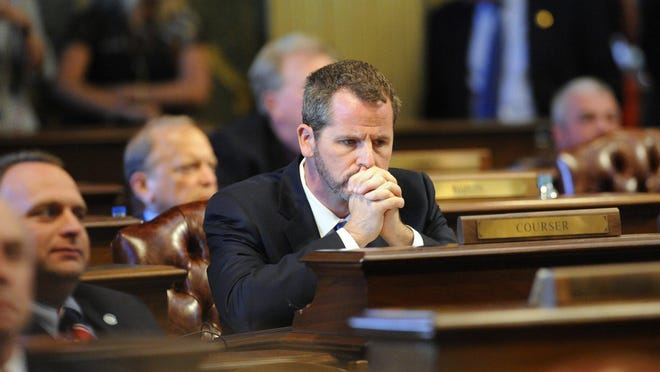 State Rep. Todd Courser waits at his desk as votes roll in on whether or not he and state Rep. Cindy Gamrat should be expelled from the state House. He resigned early Friday morning.