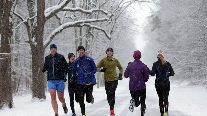 Two groups of runners pass each other on a snowy morning during early morning workouts at Eagle Creek Park Indianapolis, Saturday, December 14, 2013.
