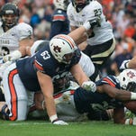 Auburn offensive lineman Shon Coleman (72) embraces Auburn quarterback Nick Marshall (14) after he scored a touchdown to go ahead 42-35 during the second half of the NCAA football game between Auburn and South Carolina on Saturday, Oct. 25, 2014, at Jordan-Hare Stadium in Auburn, Ala.