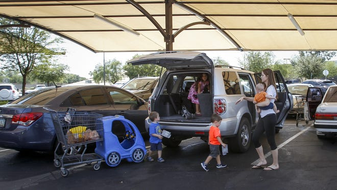 Annie McGeorge, of Phoenix, loads her car under the parking shade of the Fry's Marketplace on June 8, 2016. State Climatologist Nancy Selover found that parking under shaded structures significantly reduced vehicle interior temperatures.