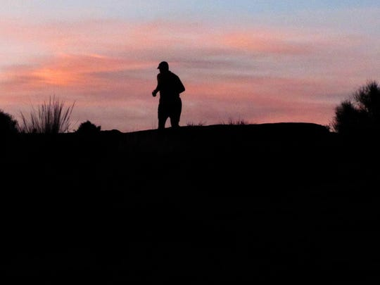 Justin Robins is silhouetted by the sunrise as he runs on the Prospector Trail in the Red Cliffs Desert Reserve Wednesday, May 27, 2015.