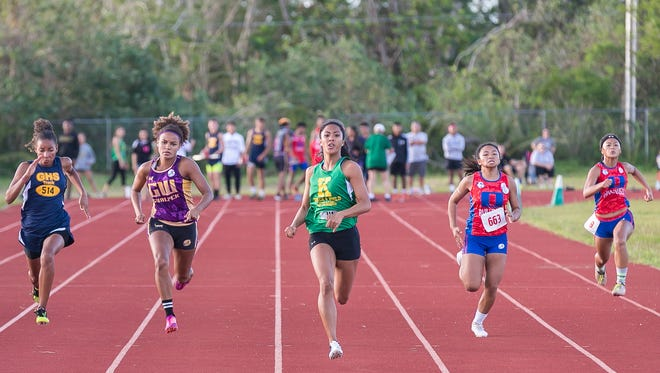 Regine Tugade (green top) from JFK wins the 100 meter sprint during the IIAAG Track and Field League All-Island meet at Okkodo High School on May 29.  Tugade will be the backbone of the Islanders as the 2016 IIAAG season begins.