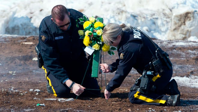 Members of the Royal Canadian Mounted Police lay flowers at the intersection of a crash site near Tisdale, Saskatchewan, Sunday. A bus carrying the Humboldt Broncos hockey team crashed into a truck en route to Nipawin for a game Friday night killing multiple people and sending over a dozen more to the hospital.