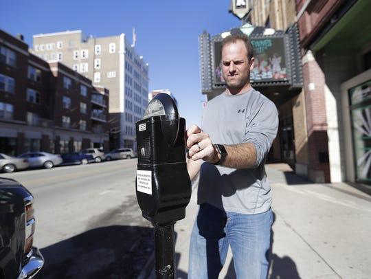 Troy Lasecki feeds a parking meter on the east side
