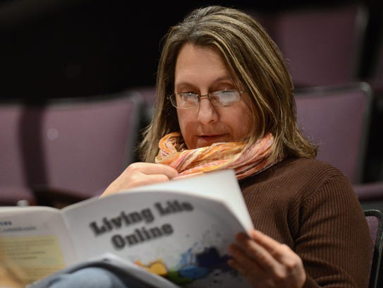 Local mother Amy Towle reads some of the distributed