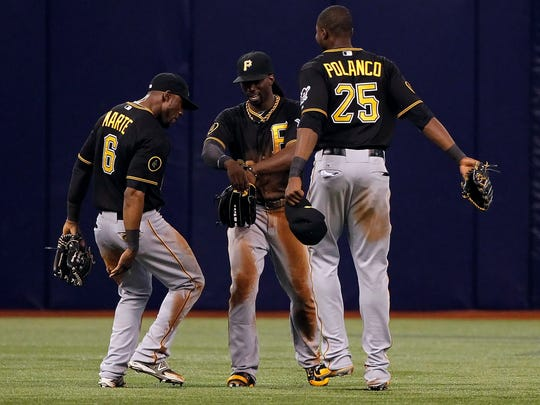 Pittsburgh Pirates left fielder Starling Marte (6), center fielder Andrew McCutchen (22) and right fielder Gregory Polanco (25) celebrate after they beat the Tampa Bay Rays at Tropicana Field, June 23, 2014.