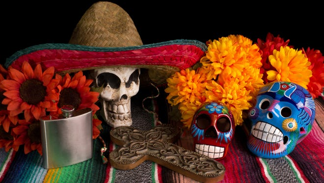 Traditional Dia De Los Muertos (Day of the Dead) alter/offering. With marigold & red sunflowers, colorful lumineras, decorative cross, tequila flask, & skull wearing Mexican sombreo.