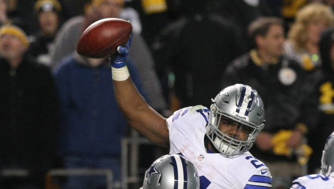 Dallas Cowboys running back Ezekiel Elliott (21) is hoisted by center Travis Frederick (72) after scoring the game-winning touchdown against the Pittsburgh Steelers during the second half of their game at Heinz Field.