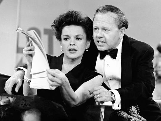 In this June 26, 1963, file photo, Judy Garland and Mickey Rooney put their heads together over a script for their first onstage reunion in 18 years, for the taping of a variety show for CBS.