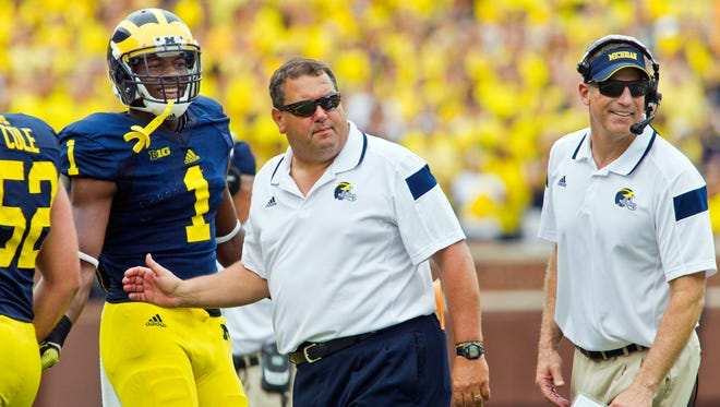 Michigan wide receiver Devin Funchess (1) stands with coach Brady Hoke on Aug. 30, 2014.