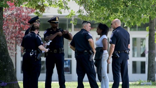 A student talks with police after a large fight broke out at East High School during a fire alarm.