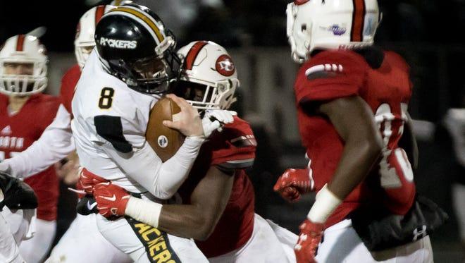 North Gwinnett High School's Jayden Mcdonald (8) tackles Colquitt High School quarterback Steven Krajewski (8) during a Class AAAAAAA football championship game, Friday, Dec. 15, 2017, in Suwanee, Georgia.