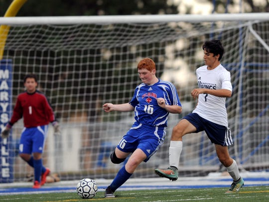Saints' Ryan Johnson tries to clear the ball as Vikings' Michael Lansky closes in Monday, Sept 28, during high school soccer action at Marysville.