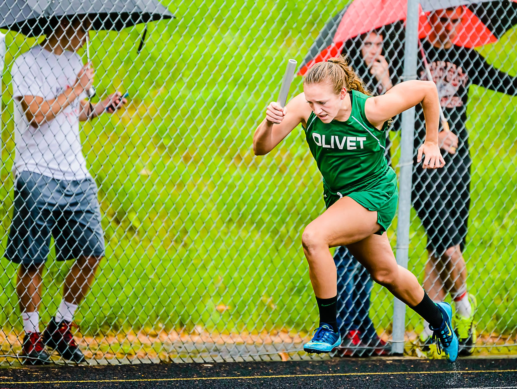 Logan Kyre of Olivet leaps out of the blocks as she begins her leg in her finals heat of the 4x100 meter relay.