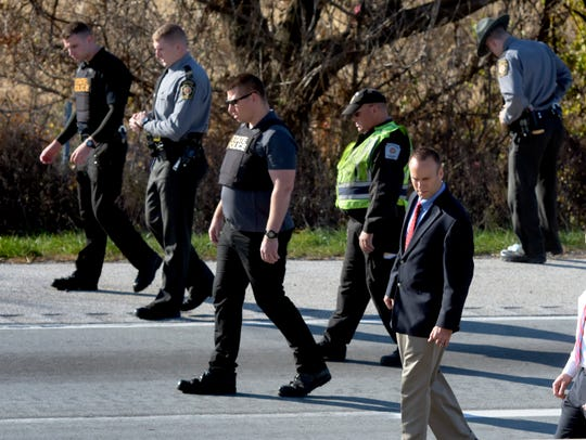 State Police walk along a closed southbound I-83 searching