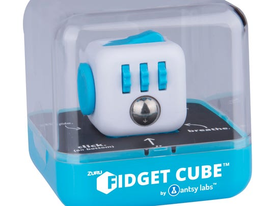 """Antsy Labs Original Fidget Cube Ages 3 and older Antsy Labs has created another addictive fidget toy. The Original Fidget Cube ($12.99) features six sides with multiple buttons, dials and switches. It's available in eight colors and also comes in a collection of designs inspired by popular superhero characters Spider-Man, Hulk, Iron Man, Captain America, Wonder Woman, Superman and more. Available at Target, Toys """"R"""" Us and Walmart"""