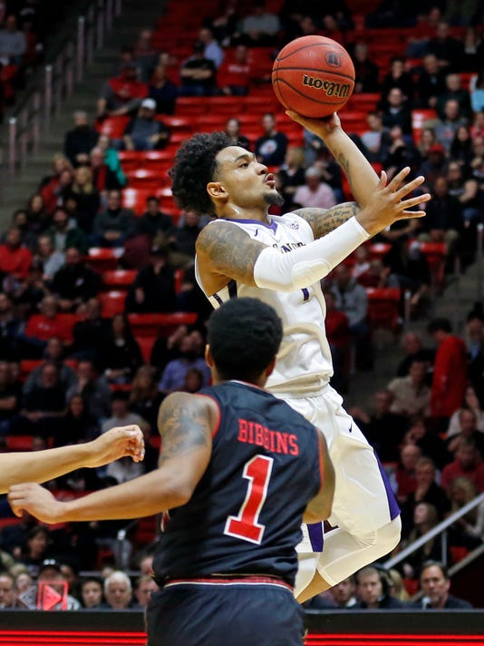 Washington guard David Crisp, top, shoots as Utah guard Justin Bibbins (1) looks on in the first half during an NCAA college basketball game Thursday, Jan. 18, 2018, in Salt Lake City. (AP Photo/Rick Bowmer)