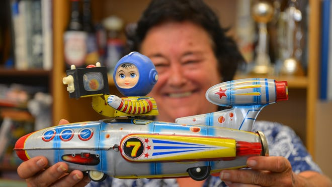 Emily Adams Perry shows some of her private space toy and memorabilia collection to advance the Space Collectibles Show and Sales August 11th at the Sands Space History Center to benefit the Air Force Space & Missile Museum Foundation. Emiy holding the toy that started her collecting - her brother sent her the 1950's-early '60's friction toy 24 years ago when she got the job at the Air Force Space and Missile Museum.