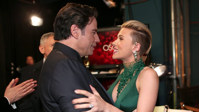 Actors John Travolta and Scarlett Johansson embrace backstage during the 87th Annual Academy Awards at Dolby Theatre on February 22, 2015 in Hollywood, California.