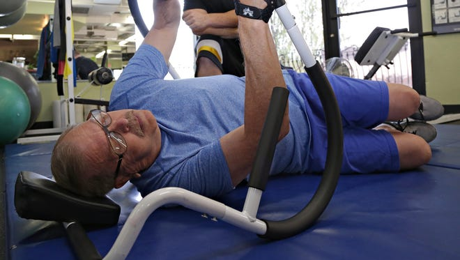 Cave Creek resident Joel Spatt, who three years ago was given six months to live after being diagnosed with an aggressive form of melanoma, works out with his personal trainer, Chris Gravink at Black Mountain Fitness as seen in Cave Creek on June 19, 2015