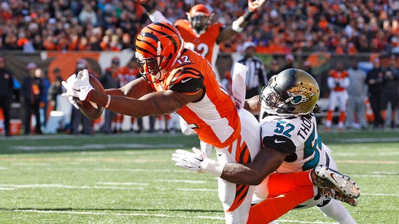 Cincinnati Bengals wide receiver Mohamed Sanu (12) dives int the end zone with a touchdown as Jacksonville Jaguars outside linebacker J.T. Thomas (52) attempts the tackle during the second quarter of their game played at Paul Brown Stadium in Cincinnati, Ohio November  2, 2014. The Enquirer/Gary Landers