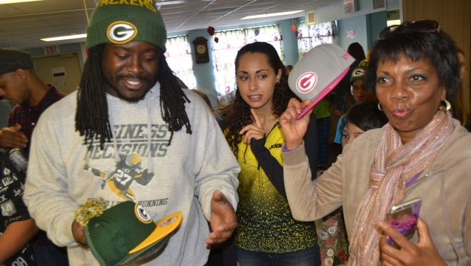 Robyn Davis, right, president of Freedom House Ministries in Green Bay, holds up one of the Green Bay Packers hats donated to the Freedom House shelter for homeless families in 2015 by then-Packers running back Eddie Lacy, left, and New Era Cap Co.