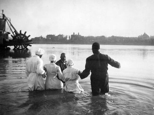 The photo exhibit shows everyday life in Cincinnati history, such as this baptism in the Ohio River in 1919.