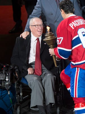 Montreal Canadiens captain Max Pacioretty, right, is presented with the flame from Senator Jacques Demers during a torch ceremony Tuesday, Oct. 18, 2016, in Montreal.