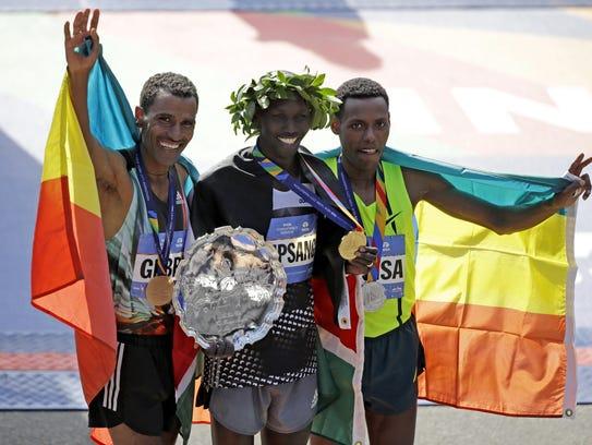Winners of the 2014 New York City Marathon. First place finisher Wilson Kipsang of Kenya, center, second place finisher Lelisa Desisa of Ethiopia, right, and third place finisher Gebre Gebremariam of Ethiopia. (AP Photo/Seth Wenig)
