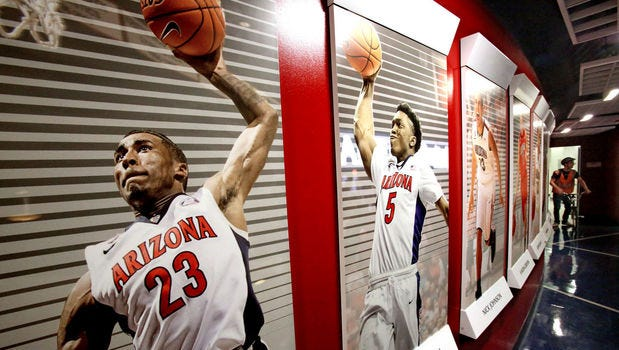 Rondae Hollis-Jefferson and Stanley Johnson, displayed on a McKale Center wall, were among those to leave early from UA.