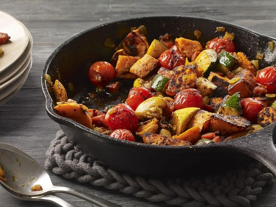 Charred sweet potatoes and summer vegetables are grilled in a cast iron skillet.