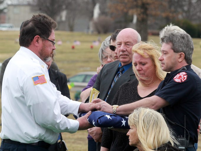 Ryland Heights and Community Fire Chief Ralph Collins (left) hands to Ryland Heights and Community Fire Department Lt. Mark Wardia the flag that was draped over the casket of Wardia's father, Vincent Wardia, Sr.,  during a service at Floral Hills Cemetery, Taylor Mill.  Vincent Wardia, Sr., 89, was a long-time chief of the department.