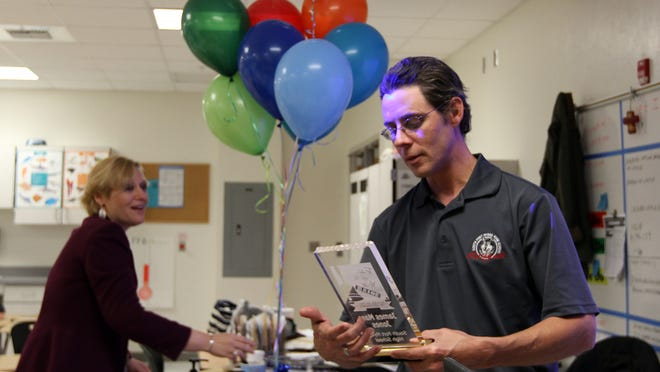 "Jones Ricardo Rolon/The News-PressJames Marc Jones, a veterinary assistant instructor at South Fort Myers High School, takes a closer look at his Teacher of The Year award. Principal Melissa Layner is in the background.James Marc Jones, a veterinary assisting instructor at South Fort Myers High School, takes a closer look at his ""2015 Teacher of The Year"" award presented by the Lee County School District. SFMHS Principal Melissa Layner is in the background."